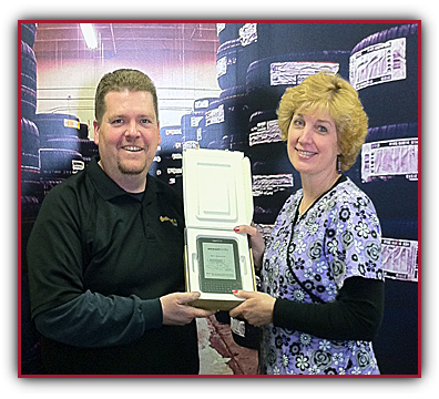 Carolyn Paulson receives her KINDLE 3G from TONY FLYNN of the Qyst LIMA location.