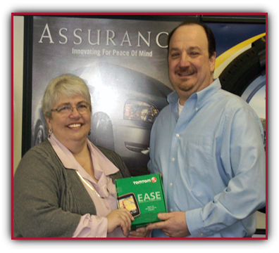 Nancy Hallowell receives her TomTom EASE GPS from Joe Giovanettir of the Qyst Upper Darby location.